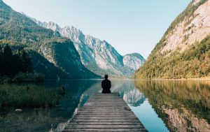 woman sitting on dock viewing water and mountains